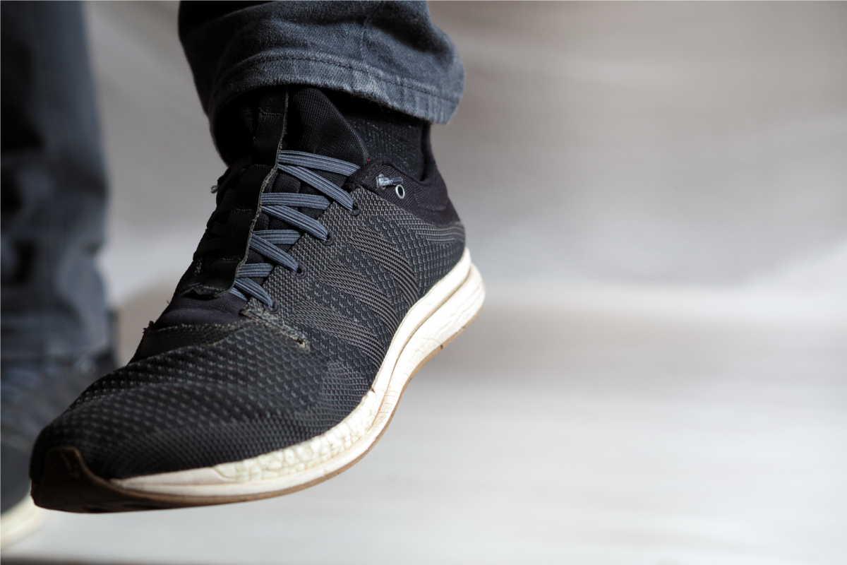 Schwarze Sneaker mit grauen leazy Schnürsenkeln in der Seitenansicht