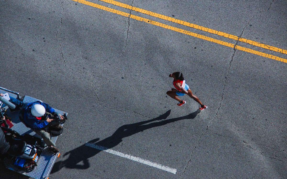 Läuferin auf Straße von oben mit großem Schatten