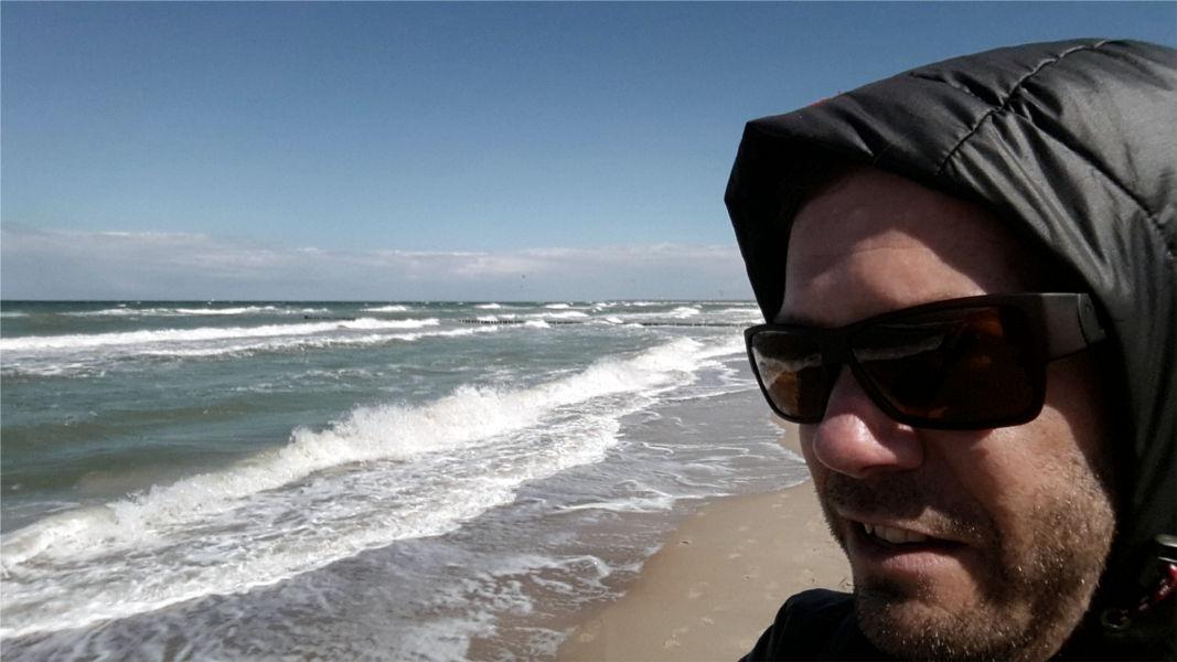 Polarisierte Sonnenbrille für Sport von gloryfy am Strand mit Meer im Hintergrund