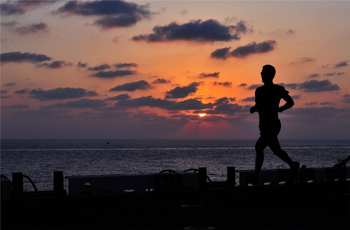 Läufer bei Sonnenuntergang am Meer