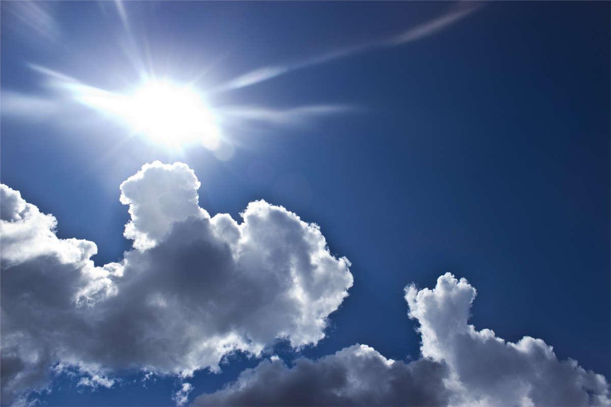 Blauer Himmel mit Sommer Sonne und einzelnen weißen Wolken
