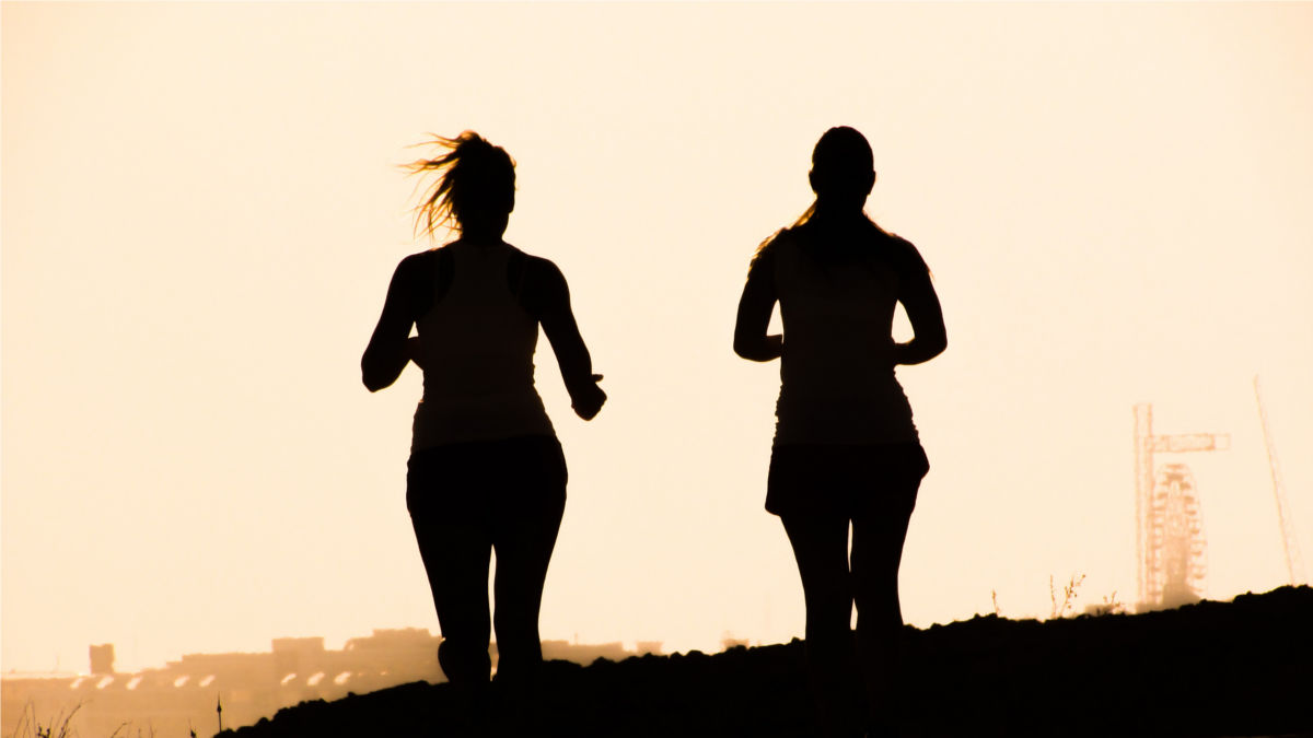 Zwei Frauen laufen an einem Sommerabend, schwarze Silouetten vor Sommerhimmel